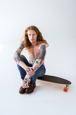 handsome shirtless tattooed skater sitting on longboard with curly hair