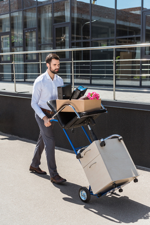 fired young manager with boxes on trolley cart Stock Photo