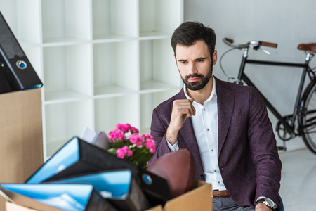 fired young businessman sitting in office and looking at box of personal stuff Imagens