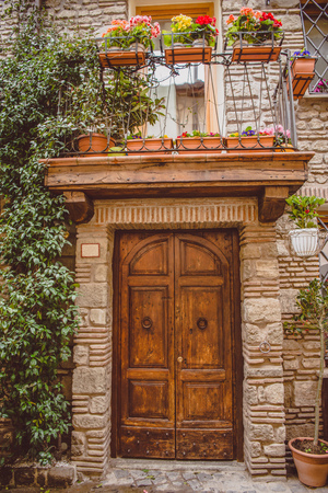 old building with wooden doors and potted plants on balcony in Castel Gandolfo, Rome suburb, Italy