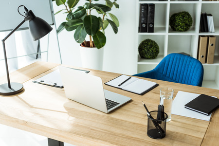 modern workplace with laptop and supplies at stylish light office