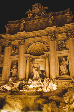 statues of Trevi Fountain with illumination in evening in Rome, Italy