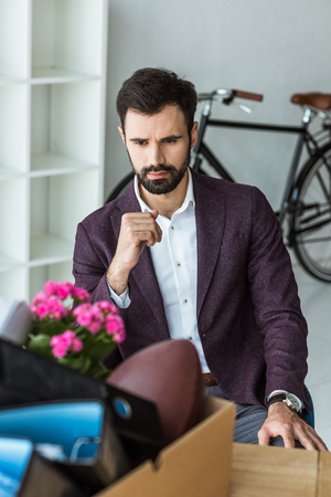 thoughtful young businessman sitting in office and looking at box of personal stuff after he gets fired Stock Photo