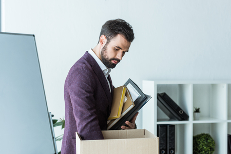 fired young businessman putting books and folders into box Stock Photo
