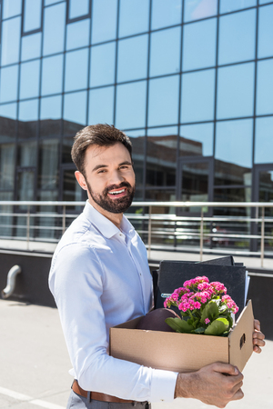 happy young manager with box of personal stuff after he was fired Stock Photo