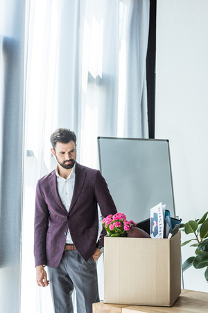 handsome young businessman looking at box of personal stuff in office Stock Photo