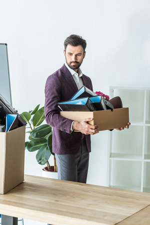 fired young businessman carrying box of personal stuff at office