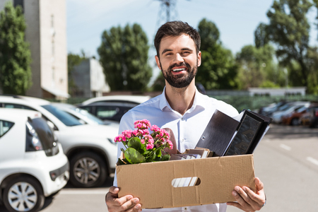 happy young manager with box of personal stuff on parking