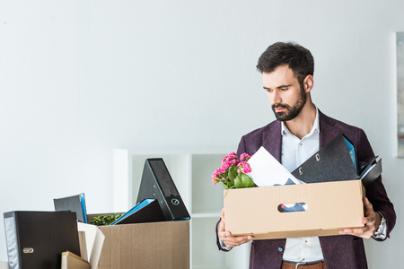 fired young businessman with boxes of personal stuff in office