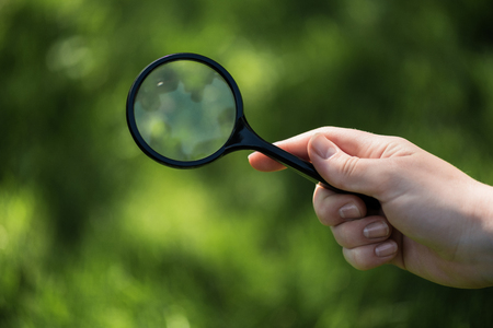 partial view of woman with magnifying glass in hand on green blurred backdrop 스톡 콘텐츠