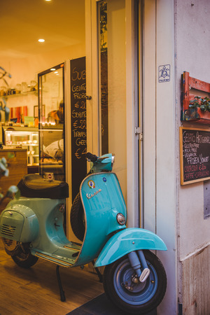 ROME, ITALY - 10 MARCH 2018: close-up shot of vintage vespa scooter parked in entrance of store at Rome