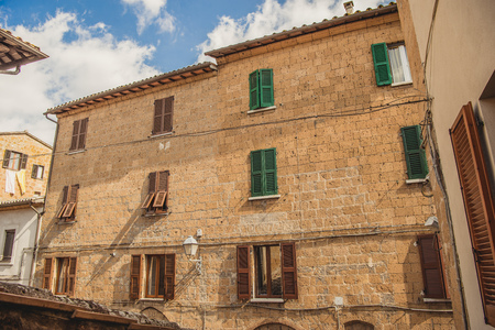 windows with brown and green shutters in Orvieto, Rome suburb, Italy