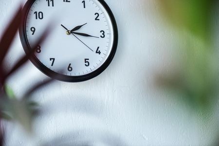 selective focus of black and white clock hanging on wall Foto de archivo