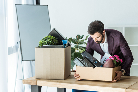 fired businessman taking box of personal stuff from desk at office