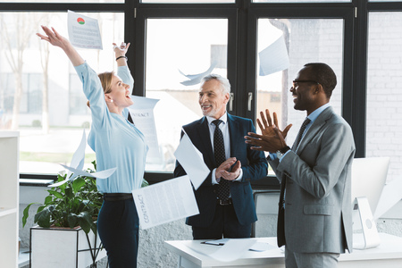 excited multiethnic business people applauding and throwing papers in office Stock Photo