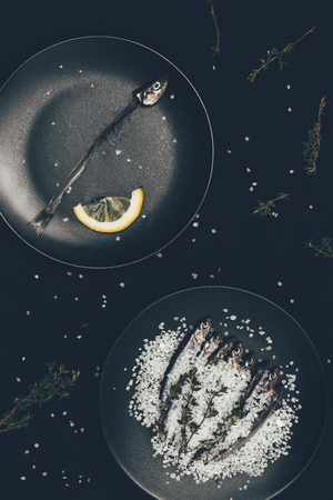 Frying pan with skeleton of fish with lemon slice and other frying pan with salted pile of fish surrounded by rosemary isolated on black