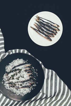 Salted pile of salted fish with rosemary in frying pan and plate with fish isolated on black Reklamní fotografie