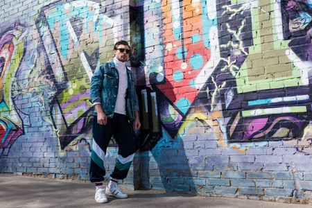 stylish young man in vintage denim jacket and track pants leaning on brick wall with graffiti Banque d'images - 106644384