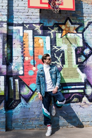 handsome young man in vintage clothing leaning on brick wall with graffiti Banque d'images - 106644518