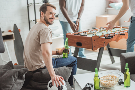 smiling young man with ball and beer sitting near friends playing table football