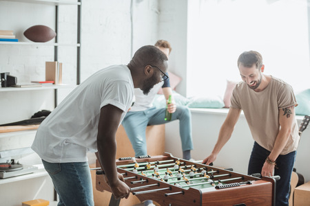 two young multiethnic friends playing table football Stock Photo