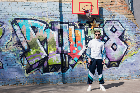 stylish young man in vintage clothing in front of brick wall with graffiti and basketball ring Banque d'images - 106644533