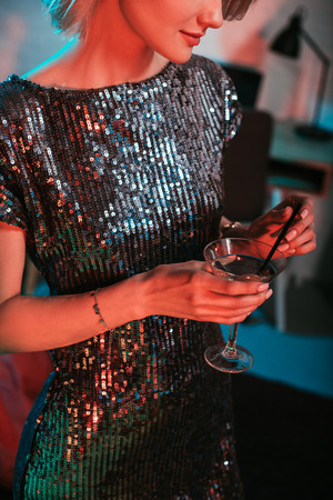 Close-up view of girl in shine dress holding glass with cocktail at party
