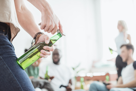 cropped image of man opening beer bottle by corkscrew 스톡 콘텐츠