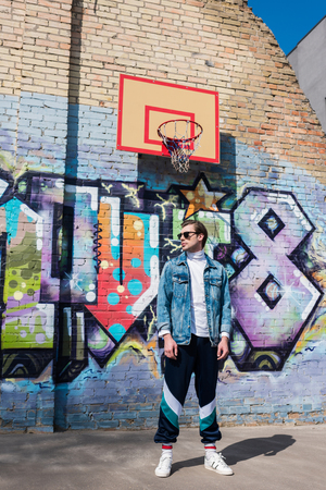 handsome young man in vintage clothing in front of brick wall with graffiti and basketball ring Banque d'images - 106644880