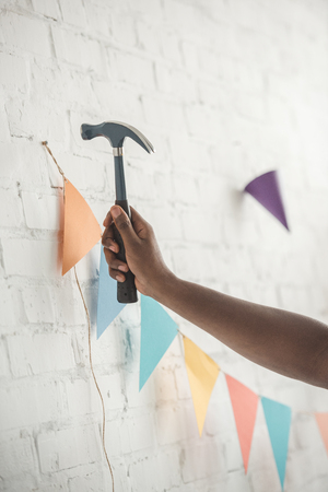 cropped image of man nailing up string with party garland on brick wall Stock Photo