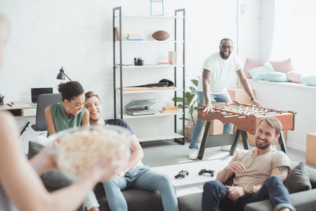 cropped shot woman with bowl of popcorn and group of young people in living room