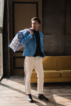 handsome young man with vintage zippered duffle bag on shoulder in loft interior