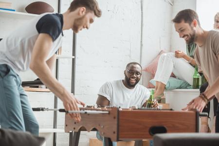 hombres jóvenes jugando futbolín mientras sus amigos miran con botellas de cerveza
