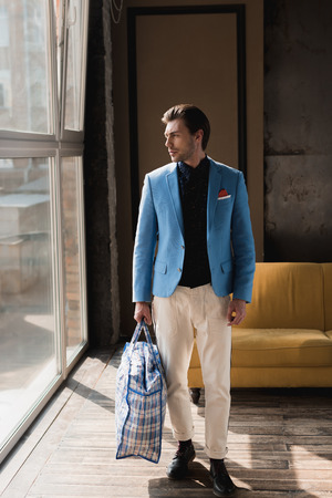 handsome young man with vintage zippered duffle bag