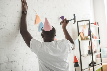 young african american man with hammer nailing up string with party garland on brick wall Stock Photo