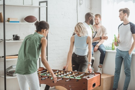 young women playing table football with male friends standing behind