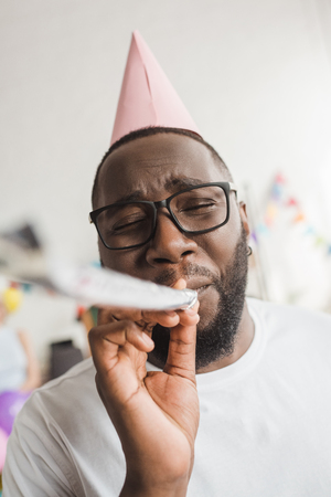 Happy african american in party hat blowing party horn Stok Fotoğraf