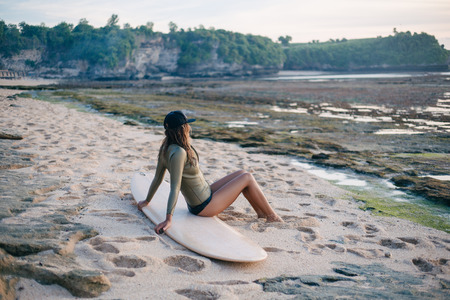 young attractive woman in wetsuit sitting on surfboard on seashore and looking at sunset