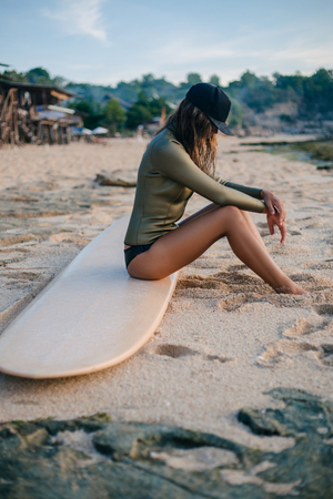 side view of young woman in wetsuit relaxing on surfboard on seashore