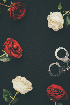 Metal handcuffs with rose flowers isolated on black Stock Photo