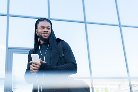 selective focus of handsome smiling african american man in earphones using smartphone on street