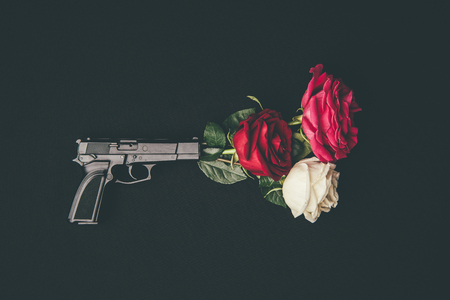 Top view of gun shooting with rose flowers isolated on black Фото со стока