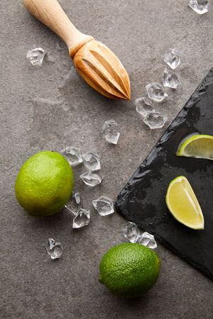 flat lay with wooden squeezer, limes and ice cubes for cocktail on grey surface Фото со стока