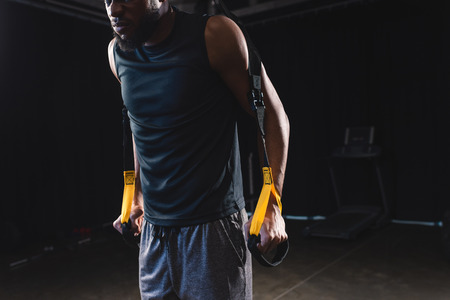 cropped shot of muscular african american sportsman training with fitness straps