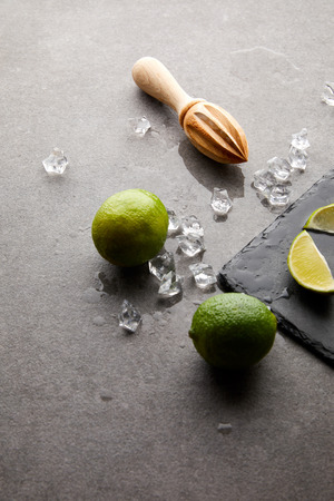 close up view of wooden squeezer, limes and ice cubes for cocktail on grey surface