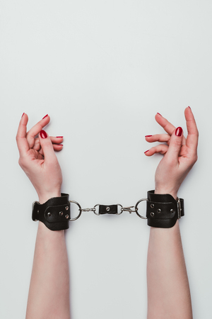Female hands tied with leather handcuffs isolated on white Stok Fotoğraf