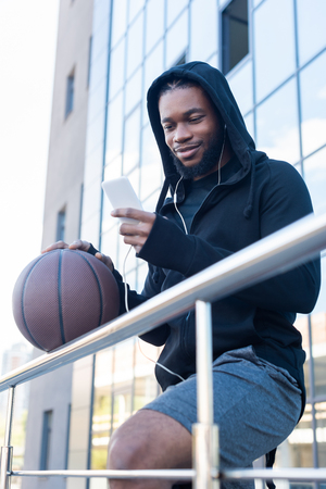 smiling african american man in earphones using smartphone while holding basketball ball on street