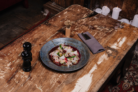 high angle view of fresh tasty Ceviche with dorado and daikon on wooden table in restaurant