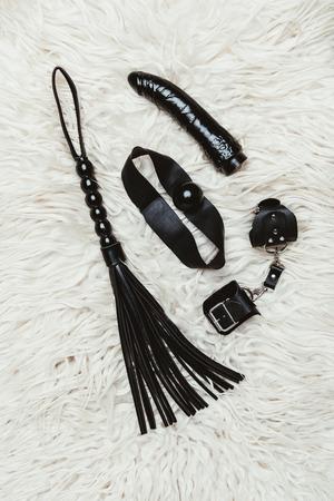 Black bdsm gag and vibrator with whip on white carpet Stockfoto