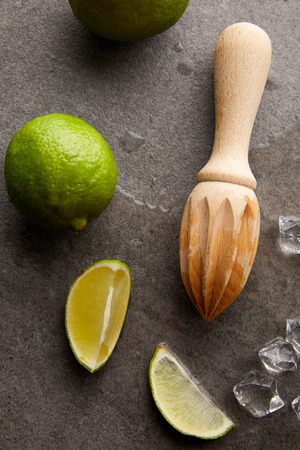 top view of wooden squeezer, limes and ice cubes for cocktail on grey surface Фото со стока